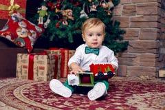 Sammanträde för litet barn på golvet nära julgranen i den vita skjortan Royaltyfri Bild