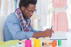 Sammanträde för modeformgivare på hans skrivbord Fotografering för Bildbyråer