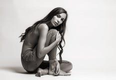 Sammanträde för modemodell på ett golv i jeans barfota på en vit Royaltyfria Foton