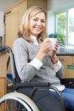 Sammanträde för rörelsehindrad kvinna i rullstol hemma med den varma drinken fotografering för bildbyråer