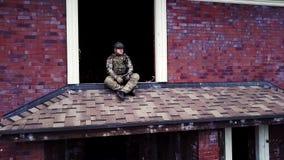 Sammanträde för soldaten för surrsikten förstörde militärt på taket byggnad i stugaby stock video