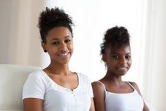 Sammanträde för tonårs- flicka för afrikansk amerikan på soffan - svart peopl Royaltyfri Bild