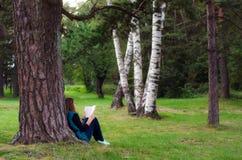 Sammanträde för tonårs- flicka under trädet och läseboken Royaltyfri Fotografi