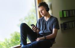 Sammanträde för tonårs- pojke på fönster och användatelefonen med hörlurar med mikrofon Arkivfoton