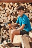 Sammanträde för tonårs- pojke på hög av vedträt arkivfoton