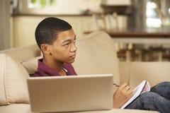 Sammanträde för tonårs- pojke på Sofa At Home Doing Homework som använder TV för stund för bärbar datordator hållande ögonen på Arkivfoto