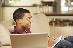 Sammanträde för tonårs- pojke på Sofa At Home Doing Homework som använder TV för stund för bärbar datordator hållande ögonen på Arkivfoton