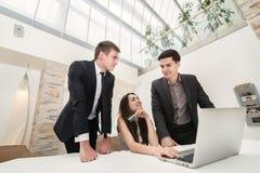 Sammanträde för tre affärsman på tabellen och sitter och håller ögonen på arbete av Arkivfoto