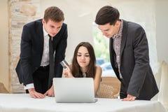 Sammanträde för tre affärsman på tabellen och sitter och håller ögonen på arbete av Arkivbild