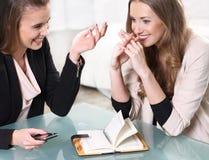 Sammanträde för två flickor på en bordlägga Fotografering för Bildbyråer