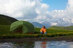 Sammanträde för ung dam nära ett tält framme av snöig bergmaxima Arkivbilder