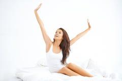 Sammanträde för ung dam på sängen och sträckningen Royaltyfri Fotografi