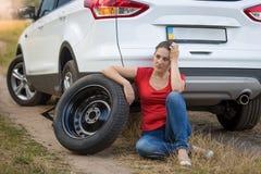 Sammanträde för ung kvinna bredvid bilen med det plana gummihjulet i fält och väntande på hjälp Royaltyfri Foto