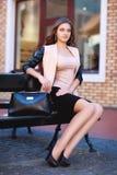 Sammanträde för ung kvinna för affär på svart bänk i gammal stad med hennes handväska, innan att shoppa Vänta någon Royaltyfria Foton
