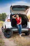 Sammanträde för ung kvinna i öppen service för automatisk för bilstam väntande på som ändrar det plana gummihjulet Royaltyfria Foton