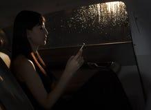 Sammanträde för ung kvinna i bilen och smsa på hennes telefon på en regnig natt i Peking Royaltyfri Foto