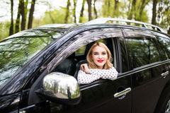 Sammanträde för ung kvinna i den nya bilen och blick från fönster arkivfoton