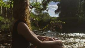 Sammanträde för ung kvinna i en flod i grunt vatten lager videofilmer