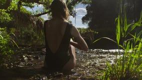 Sammanträde för ung kvinna i en flod i grunt vatten stock video