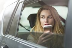 Sammanträde för ung kvinna i en taxi Royaltyfria Foton