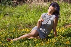 Sammanträde för ung kvinna i ett fält arkivfoton