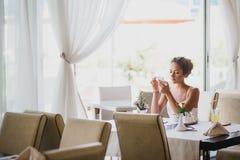 Sammanträde för ung kvinna i ett kafé genom att använda hennes telefon Arkivfoton