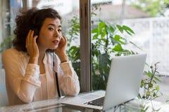 Sammanträde för ung kvinna i hörlurar med bärbara datorn Arkivfoto