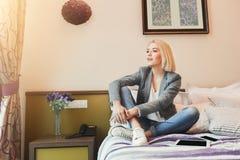 Sammanträde för ung kvinna i hotellrum Royaltyfri Bild