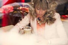 Sammanträde för ung kvinna i kafé Royaltyfria Foton