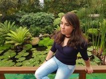 sammanträde för ung kvinna i posera för parkera arkivbild