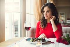 Sammanträde för ung kvinna i restaurangen som äter middag se ut fönstret arkivfoto