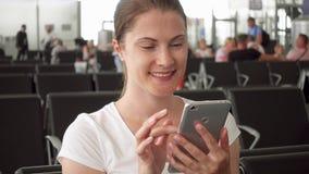 Sammanträde för ung kvinna i väntande rum för flygplats med mobilen Kvinnlig handelsresande som bläddrar på smartphonen arkivfilmer
