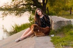 Sammanträde för ung kvinna med hennes hund som tycker om solnedgång royaltyfria foton