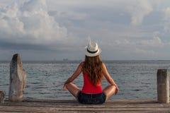 Sammanträde för ung kvinna med korsade ben och tycka om solnedgången på havet Royaltyfri Bild