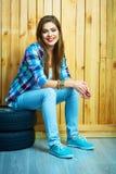 Sammanträde för ung kvinna på auto gummihjul mot träväggen Arkivfoton