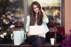Sammanträde för ung kvinna på bänken och användabärbara datorn arkivfoton