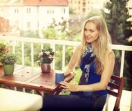 Sammanträde för ung kvinna på balkong Royaltyfri Fotografi
