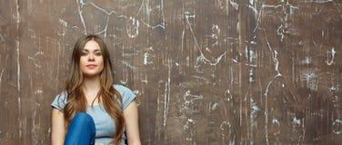 Sammanträde för ung kvinna på brun grungebakgrund Royaltyfri Foto