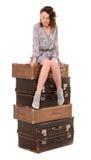 sammanträde för ung kvinna på bunt av resväskor Royaltyfria Bilder