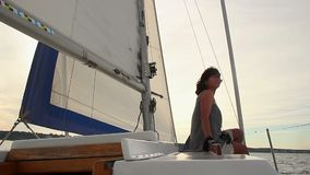 Sammanträde för ung kvinna på däcket av segelbåten som tycker om solnedgång stock video
