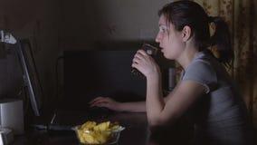 Sammanträde för ung kvinna på datoren och ätachiperna lager videofilmer