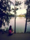 Sammanträde för ung kvinna på den blödde kusten av sjön Fotografering för Bildbyråer