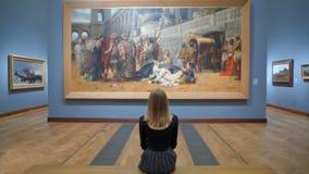 Sammanträde för ung kvinna på en bänk i Art Gallery och se en enorm bild lager videofilmer