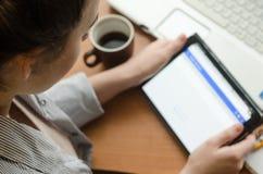 Sammanträde för ung kvinna på en bärbar dator och innehav en minnestavla i händer Arkivbilder
