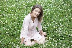 Sammanträde för ung kvinna på en grön gräsmatta royaltyfri fotografi