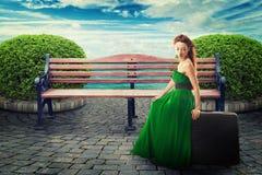 Sammanträde för ung kvinna på en resväska som väntar på en ritt Arkivfoto