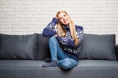 Sammanträde för ung kvinna på en soffa och se i den isolerade kameran royaltyfri bild