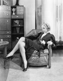 Sammanträde för ung kvinna på en stol i hennes vardagsrum som beskådar (alla visade personer inte är längre uppehälle, och inget  Arkivbilder