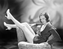 Sammanträde för ung kvinna på en stol med henne ben upp i luften (alla visade personer inte är längre uppehälle, och inget gods f Arkivbild