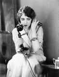 Sammanträde för ung kvinna på en stol som rymmer en telefon (alla visade personer inte är längre uppehälle, och inget gods finns  Royaltyfri Fotografi